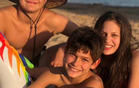 Mason Firestone '25 (bottom center), Cameron Firestone '21, and oldest brother Tyler Firestone (top left) at a beach in Harbor Springs, Michigan.