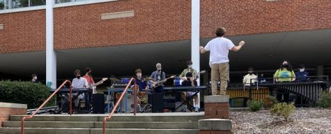 Drum Major Edward Dieser 21 conducts the War Eagle Marching Band, performing for students after school.