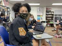 Sophomore Nia Givens '23 working on her pages in the yearbook.